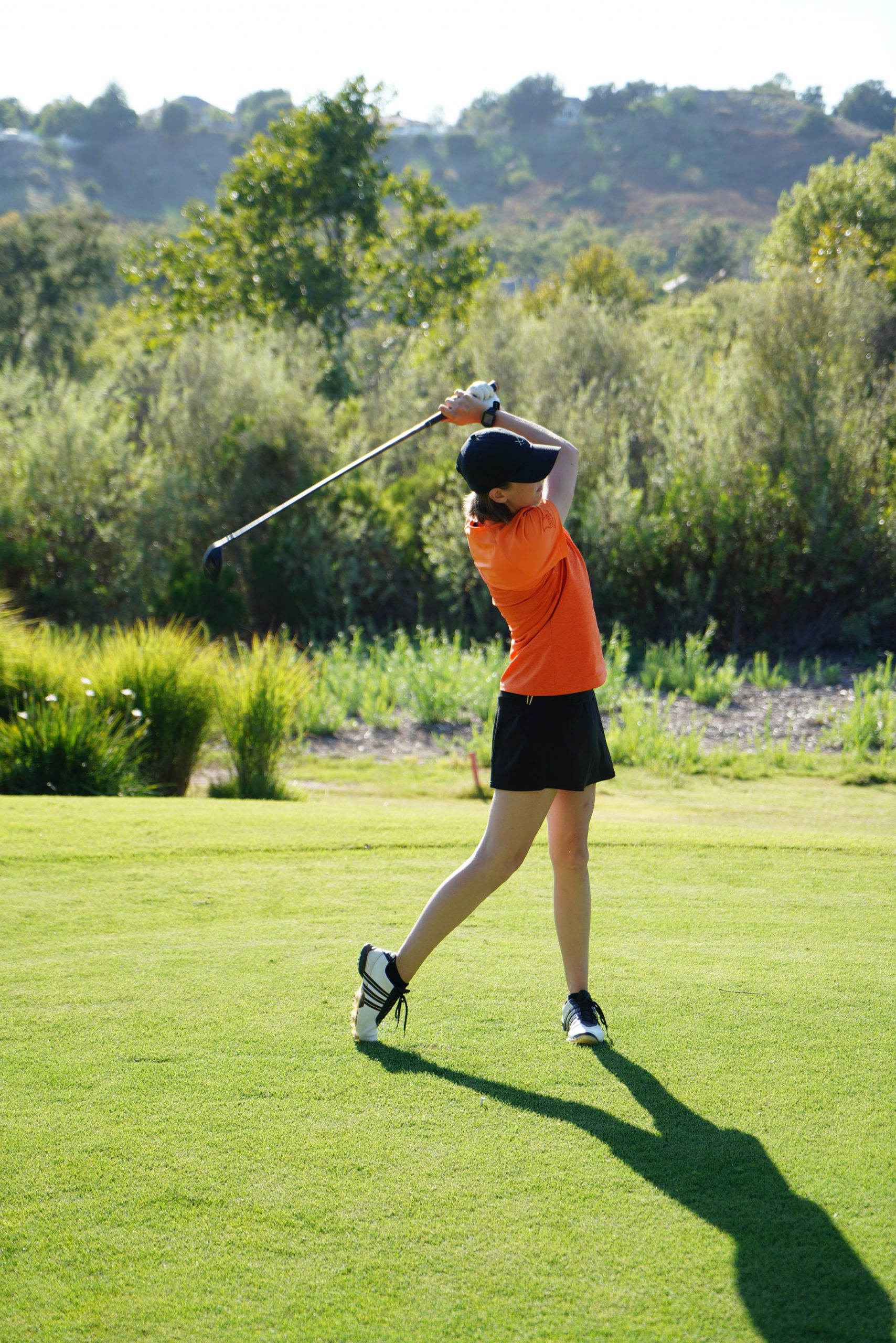 woman playing golf using single plane golf swing