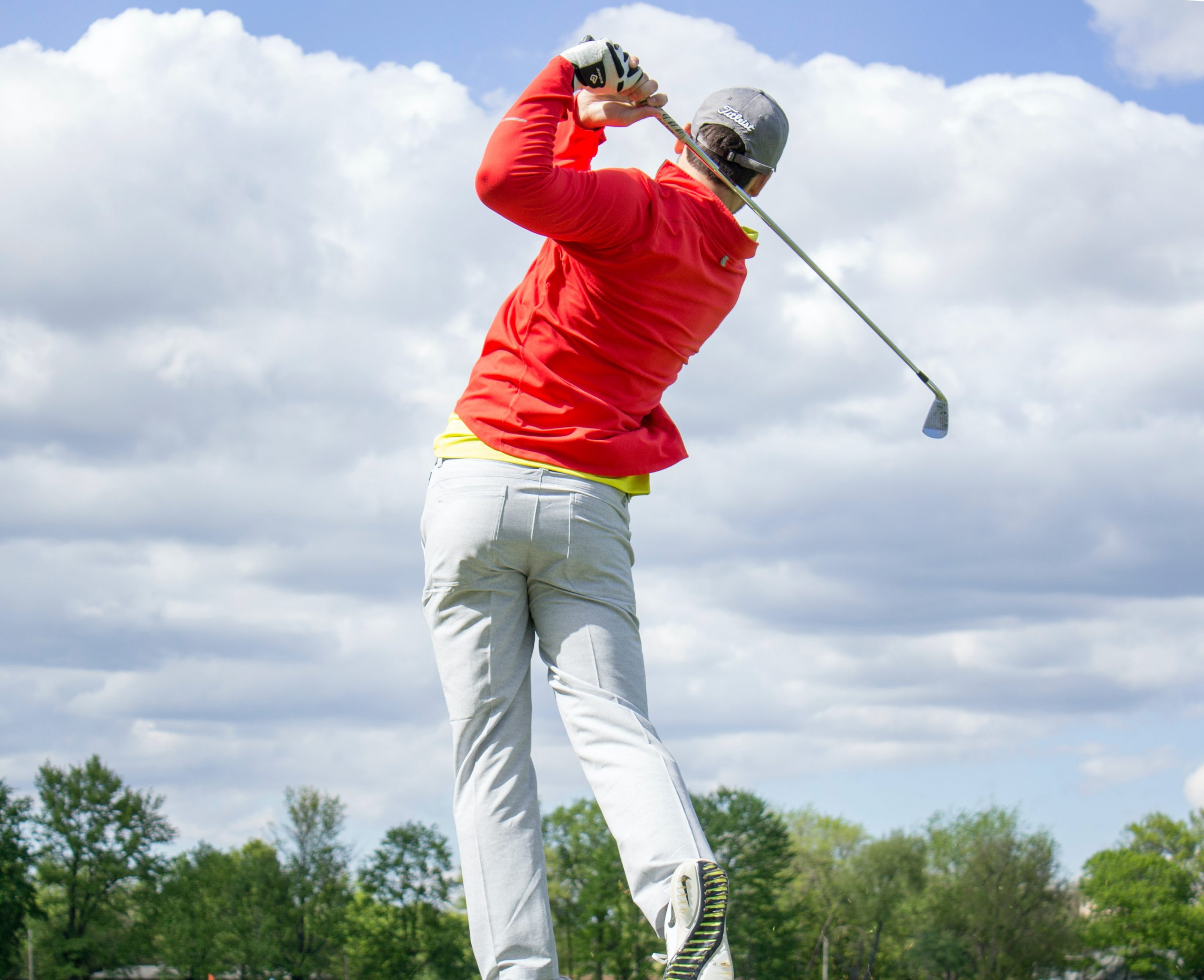 man in red long-sleeved top hitting a fade golf shot