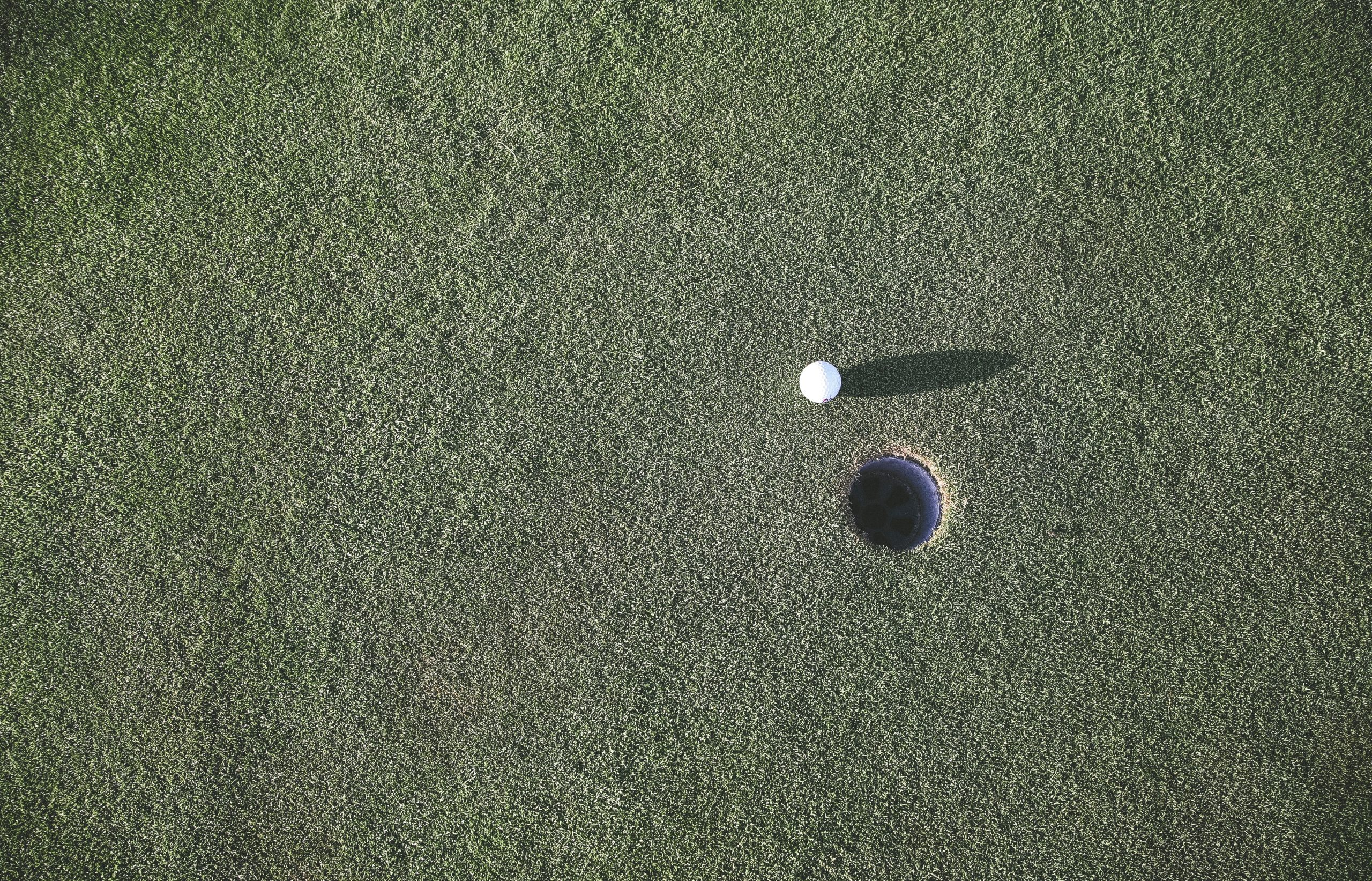 White golf ball with backspin on it near hole